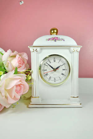 Porcelain vintage clock with roses. Stock Photo