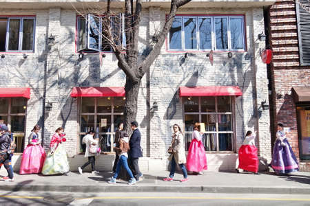 hanbok: A group of young girls in Korean traditional dress Hanbok are walking along the street of Seoul