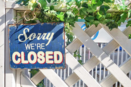 sorry: A sign written Sorry, were closed hanging on a white fence. Stock Photo