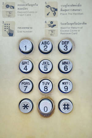 old phone: old and dirty pay phone dial Stock Photo
