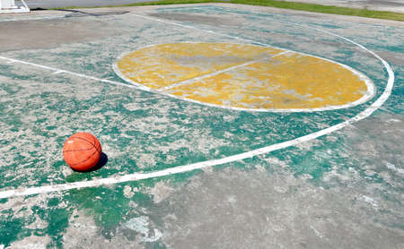 outdoor basketball court: Old outdoor basketball court with ball Stock Photo