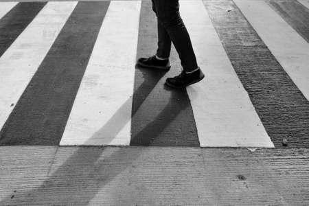crossing legs: Legs of man in black jeans and crossing street, monochrome