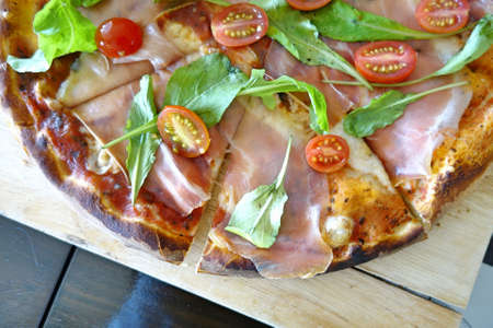 Italian parma ham pizza and rockets with thin crust. Stock Photo