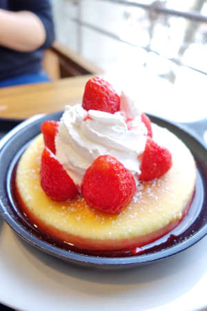 pan full of pancake with strawberry and strawberry syrup