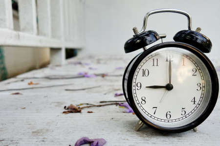 second floor: Black vintage clock on white wooden floor with fallen flower. House reflection on surface. Stock Photo