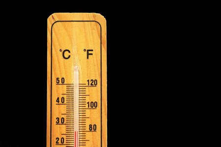 hotter: Thermometer on wooden base with celsius and fahrenheit scale isolated on black background. Stock Photo