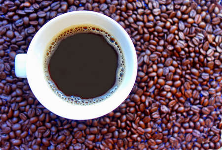 Coffee cup on coffee beans background. Stock Photo