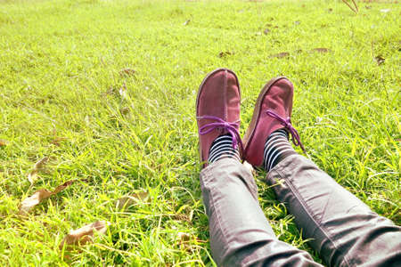 antipode: Legs with socks and shoes on green grass yard. Stock Photo