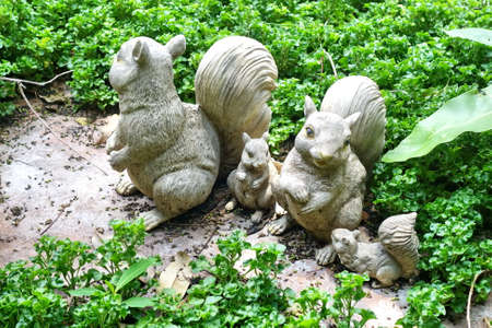 many babies: Squirrel plasters decorate in green garden.