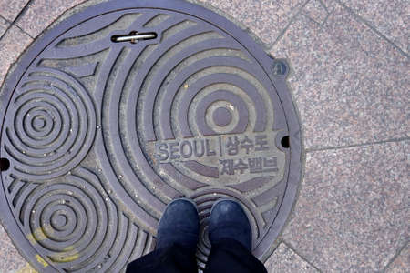 SEOUL, SOUTH KOREA : 8 December 2017 : Woman shoes standing on metal cover of drain hose in Seoul, the capital and largest metropolis of the Republic of Korea