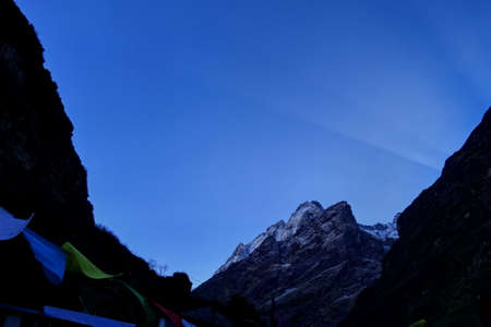 Ray of light behind Machhapuchhare or Mont.Fish Tail in Annapurna massif before sunrise in the early morning, Nepal. Stock Photo