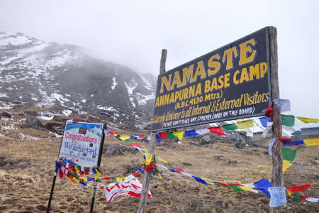 ANNAPURNA BASE CAMP, NEPAL, POKHRA - 18 APRIL 2018: Welcome sign of Annapurna base camp with prayer flags. ABC is one of a very famous trekking destination in Nepal.