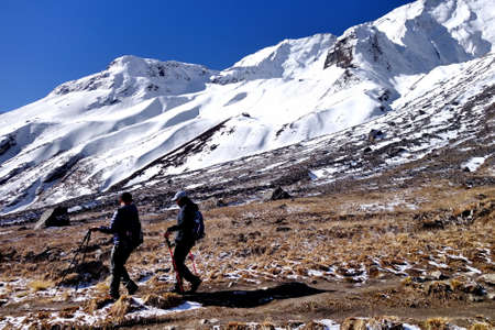 Love couple trekking together in beautiful landscape of snowy mountain.