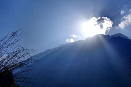 Sunrise behind mountain landscape with ray of light in Himalaya, Nepal.