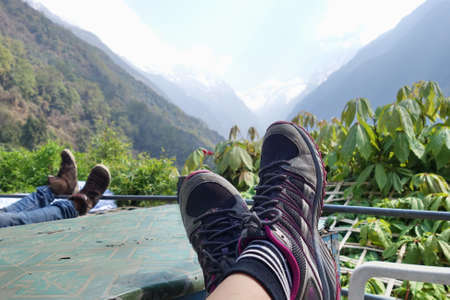 egs wearing trekking shoes with snow mountain in background. Stock Photo