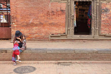 Woman tourist taking a break during the visit at an ancient city in Kathmandu, Nepal. Stock Photo
