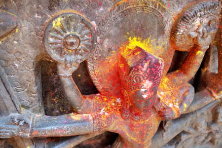 Krishna, Hindu god with yellow and red powder has been smeared on the sculpture for blessing.
