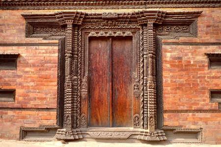 Traditional craving wood door and brick wall in Kathmandu, Nepal