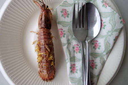 cooked crayfish on plate with fork , spoon and napkins Stock Photo