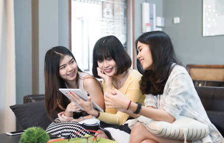 Group of young asian female friends in coffee shop,Using digital devices,chatting with their smartphone Stockfoto