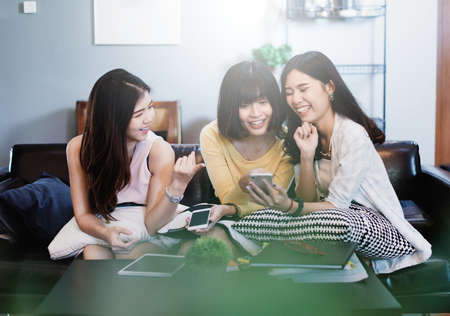 Group of young asian female friends in coffee shop,Using digital devices,chatting with their smartphones