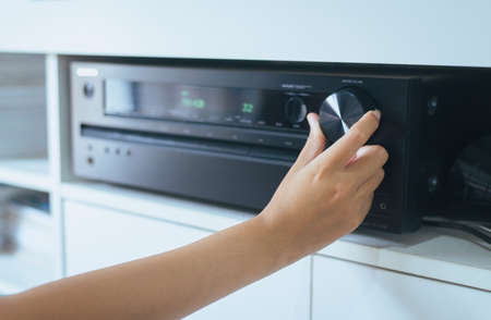 Hand turning on Home-theater amplifier system 스톡 콘텐츠