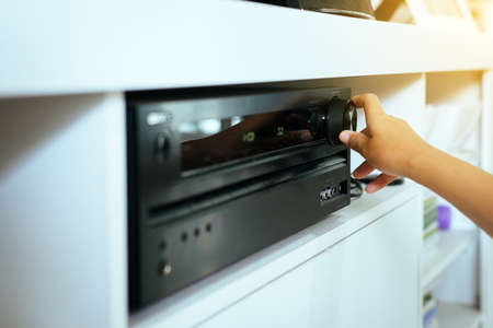 Hand turning on Home-theater amplifier system Stockfoto