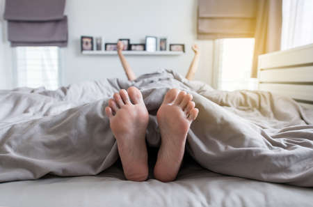 Close up of  barefoot,Feet and stretch lazily on the bed after waking up Banque d'images