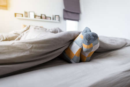 Close up of foot with colorful socks,Feet and stretch lazily on the bed after waking up Stock Photo