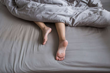 Close up of  barefoot,Feet and stretch lazily on the bed after waking up Stock Photo
