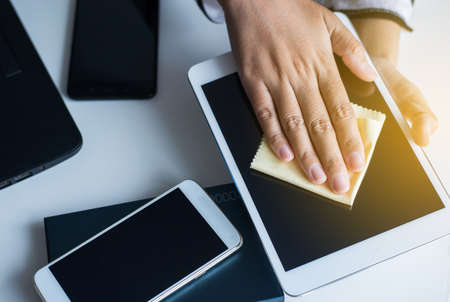 Hand woman cleaning tablets dirty on screen with microfiber cloth Stock Photo