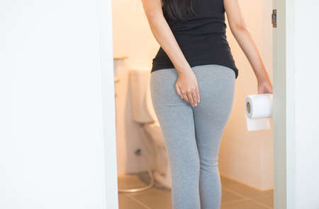Female holding toilet paper and using toilet in morning,Pants is hanging on her legs