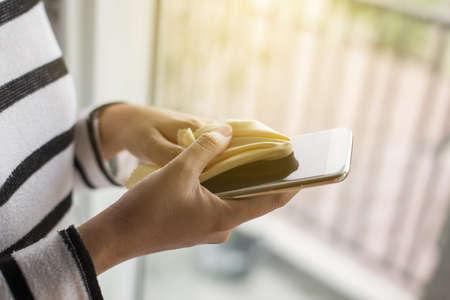 main féminine nettoyage son téléphone portable sur l & # 39 ; écran avec un chiffon en microfibre