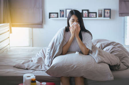 Young asian woman with cold blowing and runny nose on bed,sick female sneezing,Concept of health Stock Photo