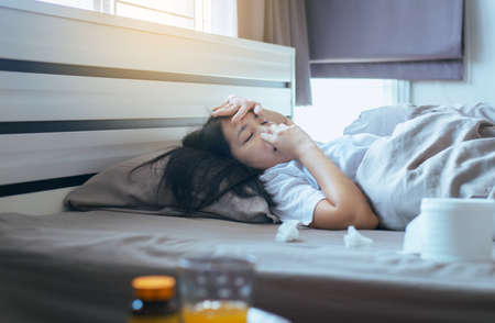 Young asian woman with cold blowing and runny nose on bed,sick woman sneezing,Concept of health Standard-Bild