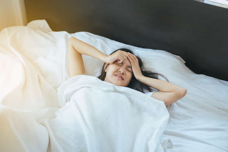 Asian woman have a headache on bed after wake up in the morning Standard-Bild