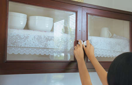 Woman with hand opening Built-in cabinet interior decoration in kitchen