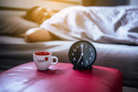 Close up of alarm clock with woman sleeping on bed blur background