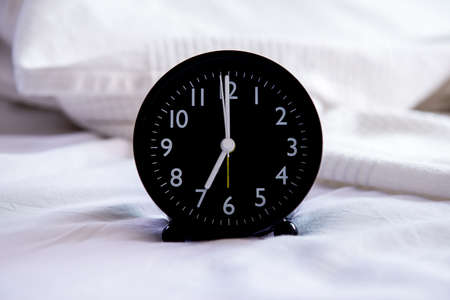 Close up of black alarm clock on the white bed Stock Photo