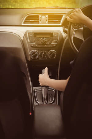 Close up of hands wman holding steering wheel and on automatic gear shift ,Driving a car