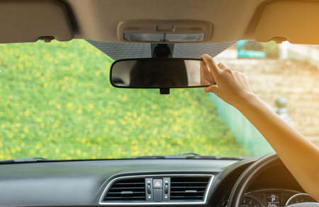 Hand woman using rear view mirror in the car,Transportation and vehicle safety concept,Selective focus Banco de Imagens