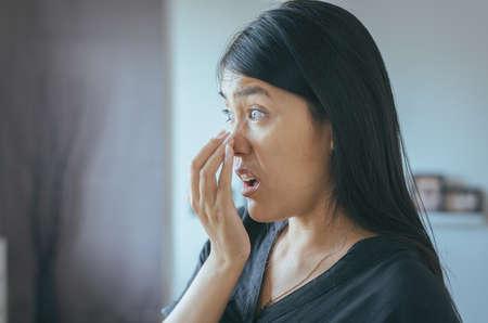 Vrouw bedekt mond en ruikt haar adem met handen na het ontwaken, slechte geur Stockfoto