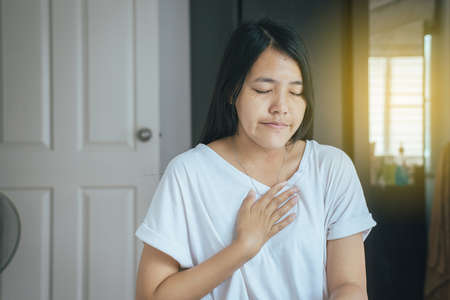 Gastroesophageal reflux disease,Because the esophageal sphincter that separates the esophagus and stomach dysfunction,Asian female having or symptomatic reflux acids Banco de Imagens