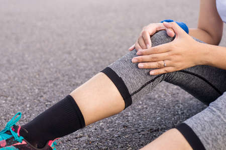 Woman suffering from pain in leg injury hands touching her knee after sport exercise running jogging and workout outdoor