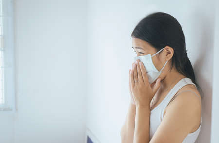 Concept of health woman using protective mask with cold blowing and runny nose on bed,sick woman sneezing