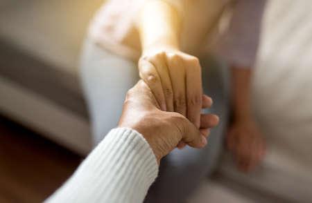 Hombre dando la mano a la mujer deprimida, psiquiatra tomados de la mano del paciente, concepto de atención de salud mental, enfoque selectivo