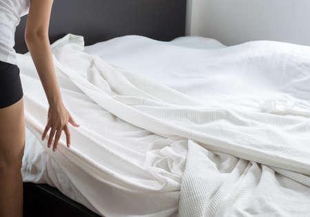 Faire un lit, femme faisant son lit dans la chambre après le réveil