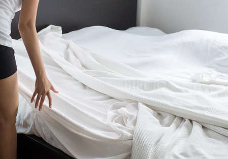 Make a bed,Woman making her bed in room after wake up Stock Photo