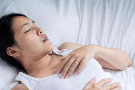 Asiatische Frau schnarcht, weil wegen der Arbeitsmüdigkeit weibliche Schnarchen beim Schlafen auf dem Bett