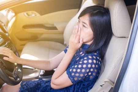 Main de femme asiatique tenant sa bouche et son nez à cause d'une mauvaise odeur en conduisant une voiture Banque d'images